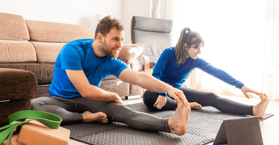 Couple exercising in living room following video from tablet woman and man stretched out on exercise mat with tablet and yoga blocks