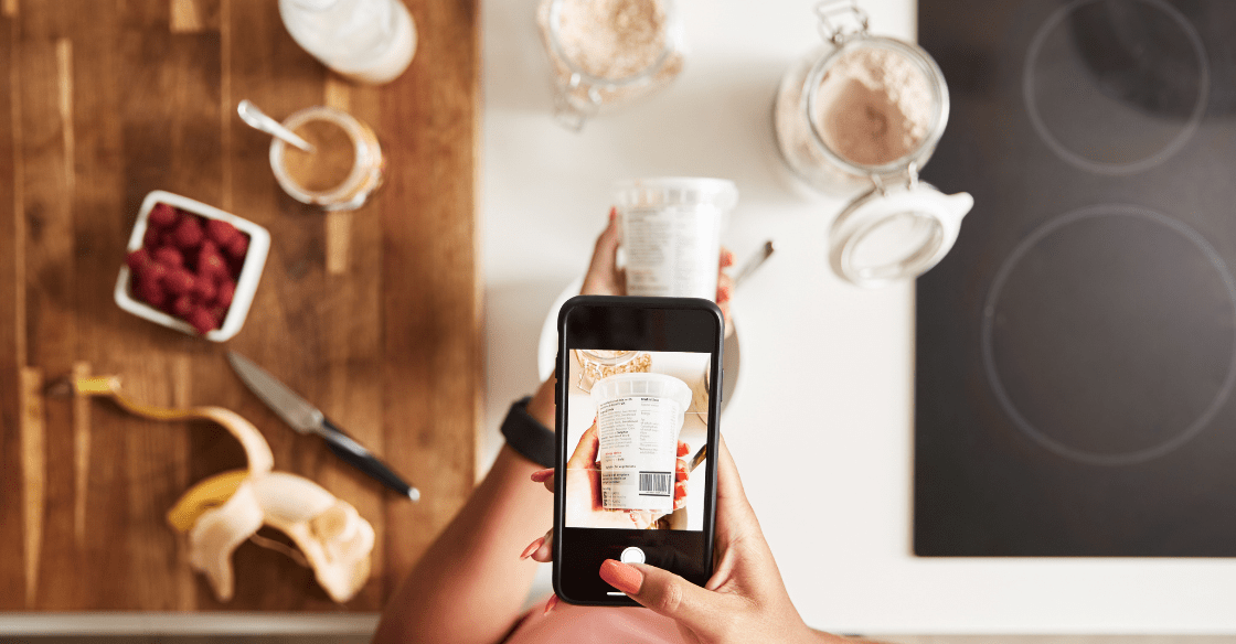 Woman Scanning QR Code On Food Packaging To Find Nutritional Information