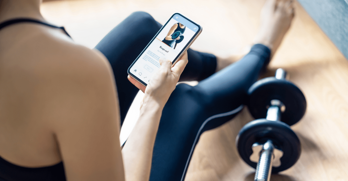 Woman doing a home gym workout with online exercise app in phone