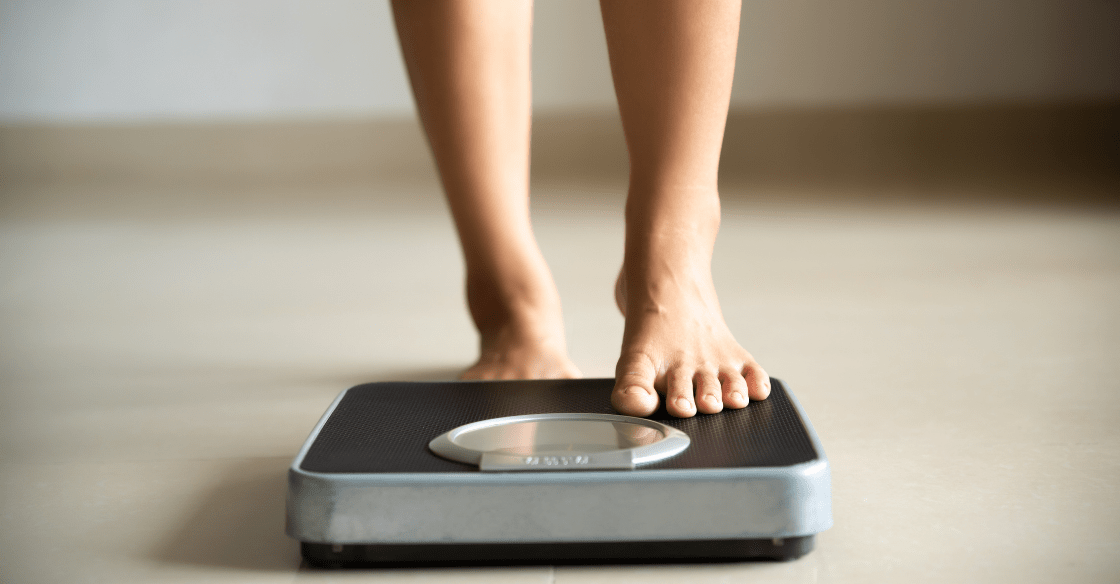 Woman stepping on scale after bariatric surgery
