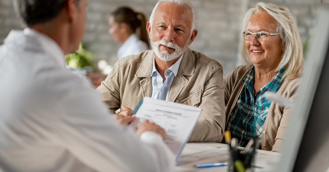 An elderly couple meets with a doctor to find out if their medicare plan covers bariatric surgery.
