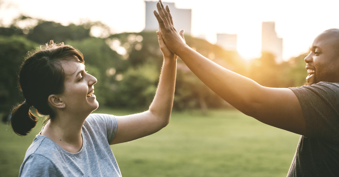 Friends in a bariatric surgery support group high-five following a workout.